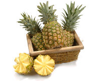 Basket with pineapples. A basket with pineapples and two alf fruits, isolated on white Stock Images