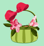 Basket with pink azaleas and bow. Green basket with azalea blossoms and pink bow on blue background Stock Photo