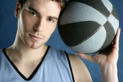 Basket player young man over blue Royalty Free Stock Image