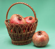 Basket with Pomegranate on green background Royalty Free Stock Photo