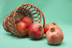 Basket with Pomegranate on green background Stock Image