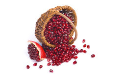 Basket with pomegranate seeds. And piece of pomegranate on white background Stock Photo