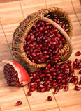 Basket with pomegranate seeds on rug. Basket with pomegranate seeds and piece of pomegranate on wood rug Stock Photography