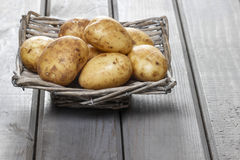 Basket of potatoes on grey wooden table Stock Photography