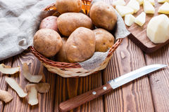 Basket with potatoes and a knife Stock Photography
