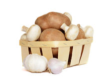 Basket with potatoes and mushrooms. Isolated on white Royalty Free Stock Photography