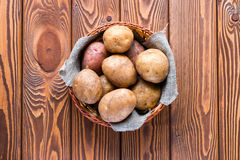 Basket with potatoes on a wooden Royalty Free Stock Images