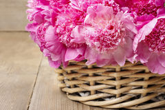 Basket of pretty pink peonies, wooden rustic background, Royalty Free Stock Photography