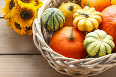 Basket of pumpkins on wooden table Stock Photography