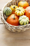 Basket of pumpkins on wooden table Stock Images