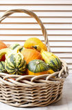 Basket of pumpkins on wooden table Royalty Free Stock Photos