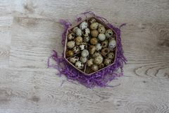 A basket with quail eggs stands on a violet decor. A lot of quail eggs lies in the basket that stands on the violet decor, on the table Royalty Free Stock Photography