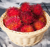 Basket of rambutan. It's a fruit that has the same texture of lychees, it is sweet and has a small seed inside just like lychees Royalty Free Stock Photo