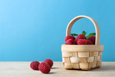 Basket of Raspberries against Blue Background Royalty Free Stock Image