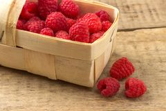 Basket with raspberries on wooden background.  Stock Photos
