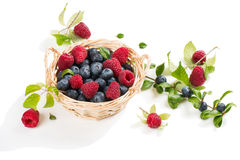Basket with raspberry and blueberry. Fresh blueberries and raspberries in a basket with green leaves  on white background Royalty Free Stock Images