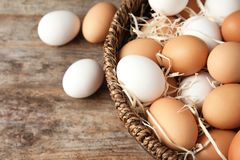 Basket with raw chicken eggs. On wooden background stock photos
