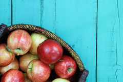 Basket of red apples sitting on wood table Royalty Free Stock Image