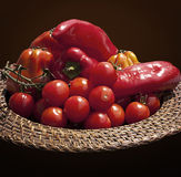 Basket with red bell peppers and cherry tomatoes royalty free stock images