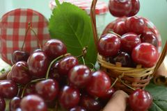 Basket with red cherries with stems and jar with cherries on yellow tablecloth Royalty Free Stock Photography