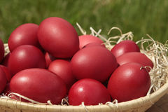 Basket with red Easter eggs. On blurry background Stock Photo