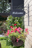 A basket with red flowers and welcome sign on a house wall.  royalty free stock image