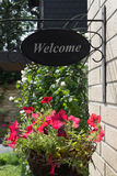 A basket with red flowers and welcome sign on a house wall.  stock photography