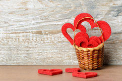 Basket with red hearts against wooden background as a Valentine'. S Day greeting with free text space Stock Photos
