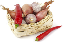 Basket with red peppers, onions and garlic bulbs. A little basket of twined reed filled with a red pepper, onions and garlic bulbs. One red pepper  before the Stock Photos