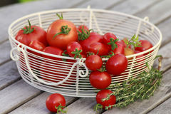 Basket with red tomatoes. A basket of red tomatoes on a table stock images