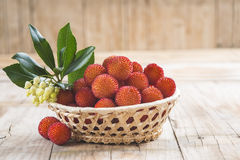 Basket with ripe arbutus unedo fruits. Leaves and floers on a wooden background Royalty Free Stock Photo
