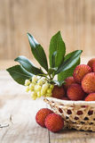 Basket with ripe arbutus unedo fruits. Leaves and floers on a wooden background Stock Photo