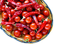 Basket of ripe cherry tomatoes and red chillies Royalty Free Stock Image