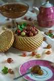 Basket of ripe red gooseberry and jam on a laid table during tea time Royalty Free Stock Image