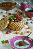 Basket of ripe red gooseberry and jam on a laid table during tea time Royalty Free Stock Photo