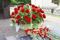 Flowers at a monument. Basket with roses and flowers at the monument Royalty Free Stock Images