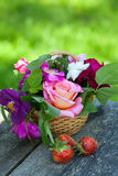 Basket with roses and strawberries on garden table Royalty Free Stock Image