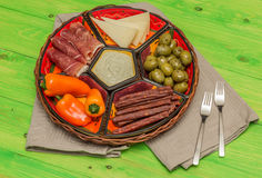 Basket with several Spanish tapas on green table Stock Photo