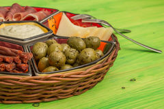 Basket with several Spanish tapas on green table Stock Photography