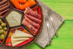 Basket with several Spanish tapas on green table Royalty Free Stock Images