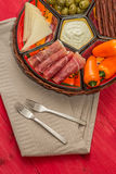 Basket with several Spanish tapas on red table Stock Photo