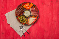 Basket with several Spanish tapas on red table Stock Photos