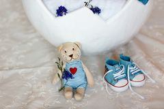 Basket shell of Easter eggs, flat shoes baby boy and a teddy bear with a heart close-up, requisites for a photo session of a newbo stock photos