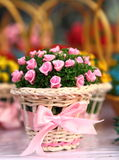Basket of Silk Roses on Table. A small wicker basket filled with pink silk roses tied with a satin bow Royalty Free Stock Photography
