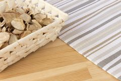 Basket with spicy dry plants on a light wooden background, covered with striped cloth royalty free stock photo