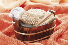 Basket with sponges, brushes and pumice on towel Stock Image