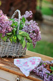 Basket of spring lilacs and floral headband on vintage bureau in spring garden Stock Image