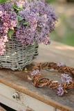 Basket of spring lilacs with handmade wreath on vintage bureau Stock Photography