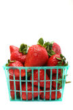 Basket of Strawberries. Strawberries in a green plastic basket, isolated against a white background Royalty Free Stock Photo