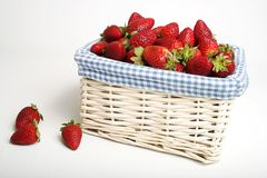 Basket of strawberries. Wicker basket with fruit royalty free stock images